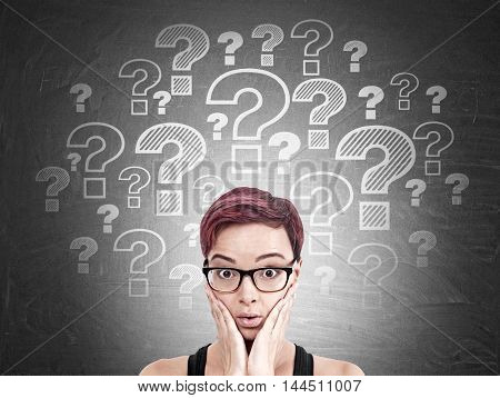 Girl with red hair wearing glasses is standing near blackboard with white question marks on it. Concept of difficult question in life. FAQ.