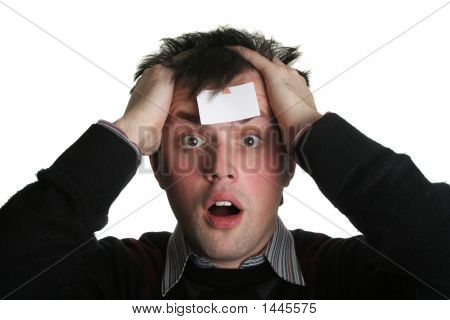 young man with crazy eyes and blank piece of paper on his forehead stock photo