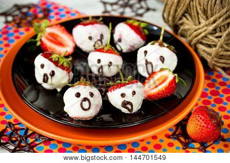 Halloween dessert - strawberry ghosts - dip strawberries in melted white chocolate selective focus