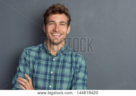 Young handsome man leaning against grey wall with arms crossed. Cheerful man laughing and looking at