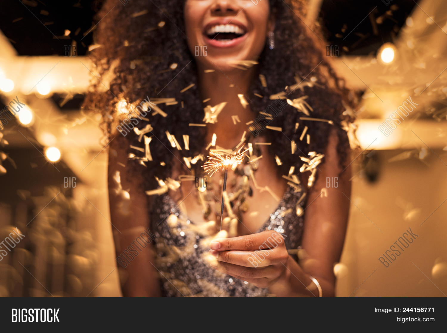 Cheerful young woman holding single sparkler in hand outdoor. Detail of african girl celebrating new