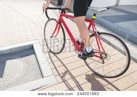 Red bike and cyclist legs close-up while riding around the city. A man rides around the city on a red bike. Traveling around the city on a bicycle. stock photo