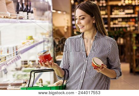 Horizontal Shot Happy Woman Reading Label With Price At Caviar Jar While Standing At Seafood Superma