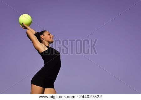 gymnastics for you. Sport and success. Woman gymnast in black sportswear with green ball. Workout of girl on blue sky background. Gymnastic school and energy. Flexibility in acrobatics and fitness health. stock photo