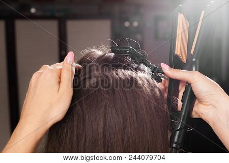 professional hairdresser clipping hair of a young model with a hairpin in a beauty salon. concept of caring treatment stock photo