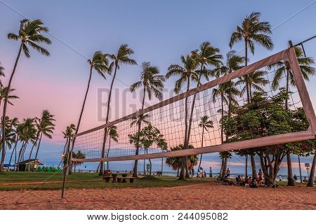 Beach volleyball net with palm trees on background at sunset. Fort DeRussy Beach Park is part of eight sections that make up the popular and long Waikiki Beach in Honolulu, Oahu, Hawaii. stock photo