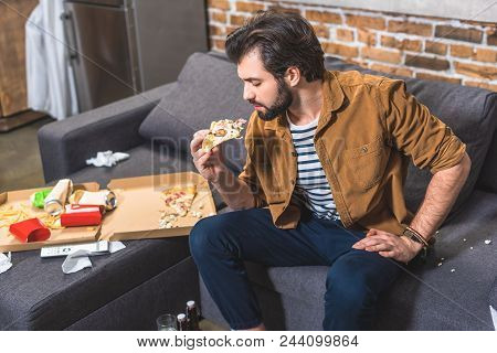 handsome loner eating pizza at living room stock photo