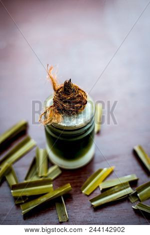 Ayurvedic and floral essence of Lemon grass or East Indian lemon grass or lili chai with its leaves on wooden surface used in many home remedies and in medicines also. stock photo
