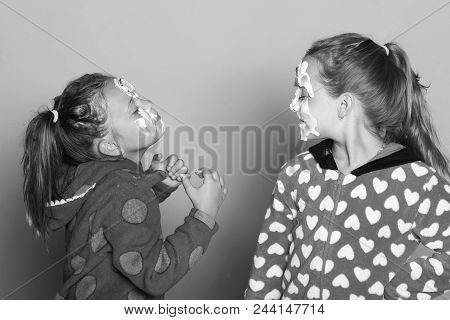 Kids pose on pink background. Girls in colorful polka dotted pajamas. Children with dreamy faces and beauty masks on, wearing pony tails. Childhood, friendship and happiness concept stock photo