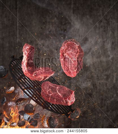 Kettle grill with hot briquettes, cast iron grate and tasty beef steaks flying in the air. Freeze motion barbecue concept. stock photo