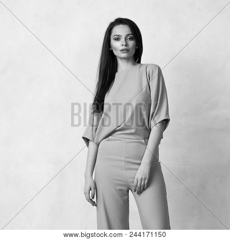 Young brunette woman with long straight hair wearing trendy short sleeved pink jumpsuit and nude heeled shoes posing against white wall on background. Female model demonstrating fashionable outfit. stock photo