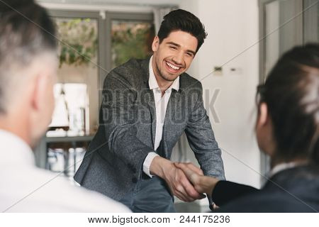 Business, career and placement concept - happy european man wearing suit rejoicing and shaking hands with group of employee when was recruited during interview in office stock photo