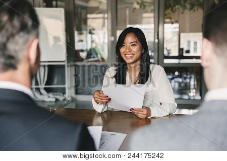 Business, career and placement concept - young asian woman smiling and holding resume, while sitting