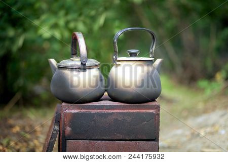 Two stained black kettle on the fire stand on the grill in the open air stock photo