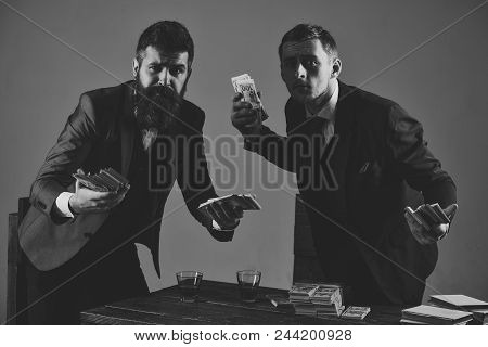 business success. Clandestine transaction with cash. Company engaged in illegal business. Men at table with piles of money and alcohol drinks. Illegal business concept. Businessmen with packs of money looks suspicious. stock photo
