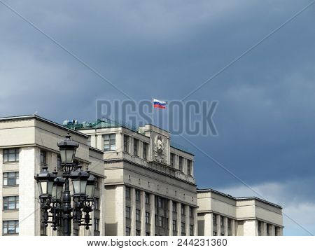 Russian flag on the Parliament building in Moscow against dark cloudy sky. State Duma, authority of Russia stock photo