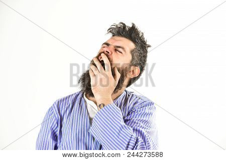 Morning yawning concept. Guy covering mouth with hand, copy space. Hipster with beard and mustache with messy hair wears bathrobe, close up. Man with yawning sleepy face on white background. stock photo