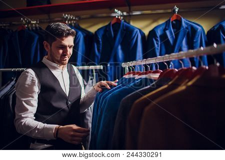 Tailor, tailoring. Men's suit, tailor in his workshop. Elegant man's suits hanging in a row. Luxury mens classic suits on rack in elegant men's boutique. stock photo