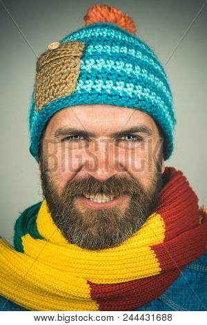 Smiling fashionable handsome bearded man in winter scarf and hat. Attractive man with scarf and hat in autumn/winter time. Men autumn/winter fashion, european style. Guy in trendy casual cap and scarf stock photo