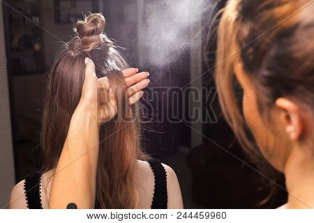 hairdresser fixing hair of a young beautiful model with a coiffure using a hairspray in a beauty salon. concept of professional stylist studying stock photo