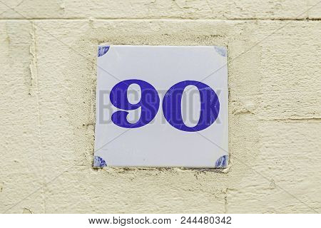 Ninety of information on a wall, detail of even number, address stock photo