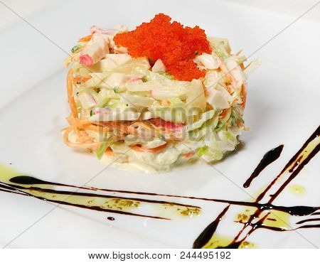 Salad with crab meat (crab meat, iceberg salad, carrots, cucumbers, pineapple, tobiko, white sauce). stock photo