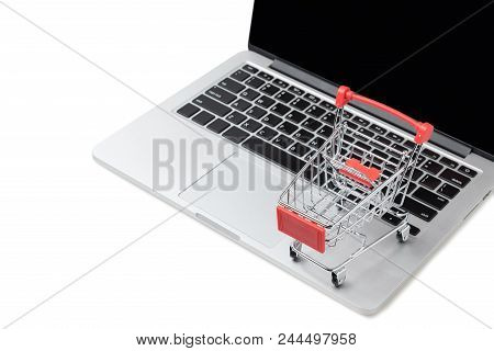 Shopping cart on a laptop keyboard isolated on white background, E-commerce, Shopping cart on laptop, Conceptual image, Ideas about online shopping stock photo