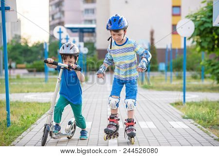Two boys sibling brothers together in park, helps boy with roller skates to stand up after fall. Friendship and active leisure summer holidays time with family concept. stock photo