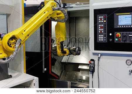CNC lathe machine and robot used for automation of loading and unloading operations. Selective focus. stock photo