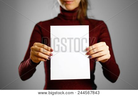 Woman showing blank white flyer paper. Leaflet presentation. Pamphlet hold hands. Girl show clear offset paper. Sheet template stock photo