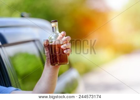 Alcohol, bottle,  car and concept of drunk driving - the person holds in hand a bottle with alcoholic drink, driving the car. Tonted stock photo