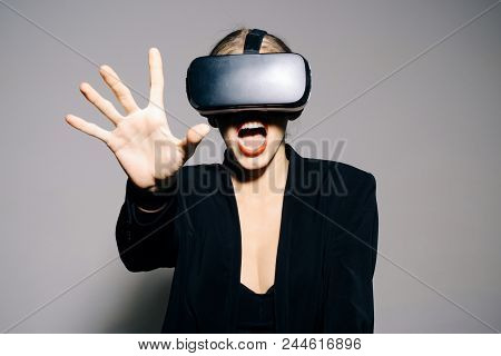 Excited attractive woman using 3d goggles watching virtual reality. Surprised woman with VR device. Amazed girl touching air during using VR-glasses virtual reality headset. Virtual reality glasses. stock photo