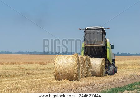 Tractor and round baler discharges. Straw Bales. stock photo