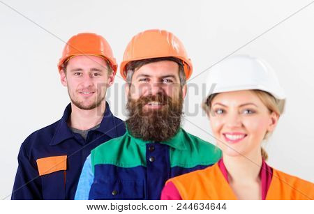 Woman and men in hard hat stand close as team. Diversity in working collective concept. Different people in team of architects, labourers, builders, happy smiling faces, isolated white background. stock photo
