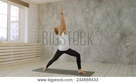 Beautiful woman doing first step of surya namaskar, sun salutation stock photo