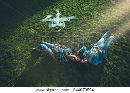 Two beautiful happy curly girls of different races are laying on the grass of summer glade lit by sunlight and recording a broadcast for their vlogs using a flying drone above them stock photo