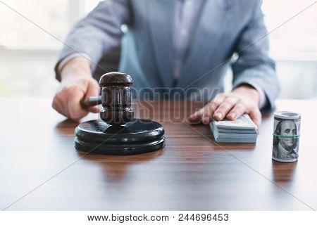 Punishment for bribery. Law-abiding moral official touching money and touching an inscribed gavel stock photo