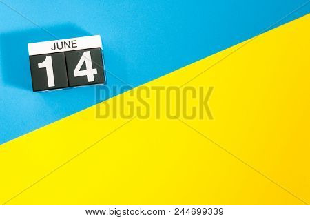 June 14th. Day 14 of june month, calendar on table with blue and yellow background. Summer time, empty space for text. stock photo