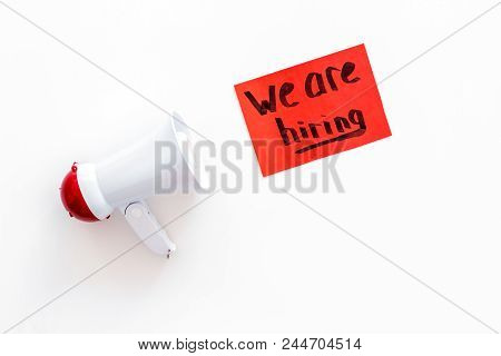 Job recruiting advertisement. We are hiring lettering near megaphone on white background top view. stock photo
