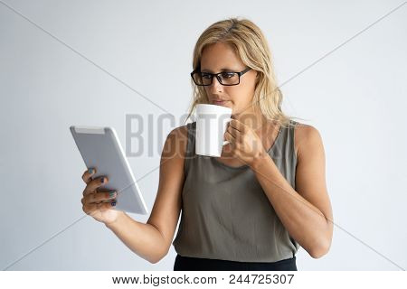 Focused female reporter reviewing news feed and drinking morning coffee. Serious woman in casual wear and glasses having coffee break and reading on tablet. Coffee break concept stock photo