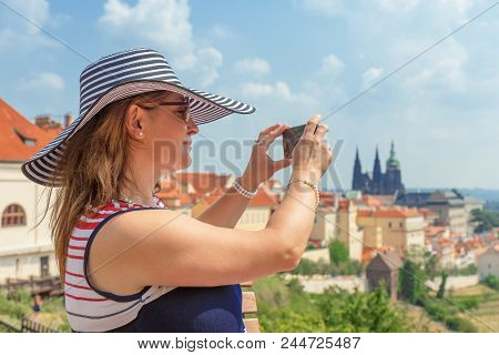 A pretty smiling elegant woman in a hat, middle aged, sitting on a lookout terrace of Strahov Monastery and taking pictures of a beautiful panorama of Prague Castle by her smartphone, sunny summer day. stock photo
