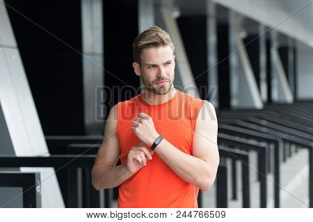 Sportsman training with pedometer gadget at stadium. Sport gadget concept. Man athlete strict face with sport equipment, urban background. Athlete fitness tracker or pedometer. stock photo