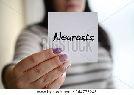 Young sad girl shows a white sticker. Caucasian brunette holding a sheet of paper with message. Neurosis stock photo