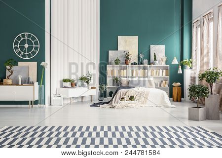 White home library with gray paintings and plants in a natural and spacious bedroom interior with turquoise green wall stock photo