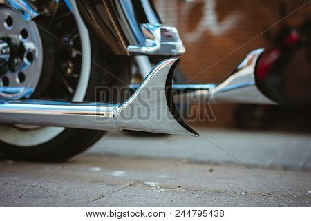 Part of luxury motorcycle. Close up of shiny chromed retro fishtail exhausted pipes. Soft lighting, vintage look. stock photo