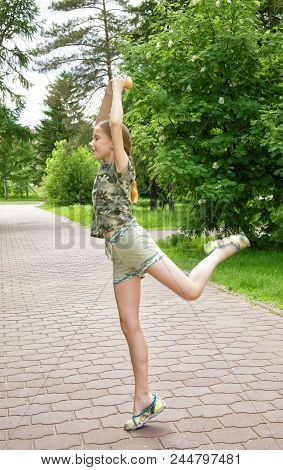 Slender teen girl with ice cream in hand dancing in the park enjoying the coming vacation. Choreographic exercises on the alley among the trees stock photo