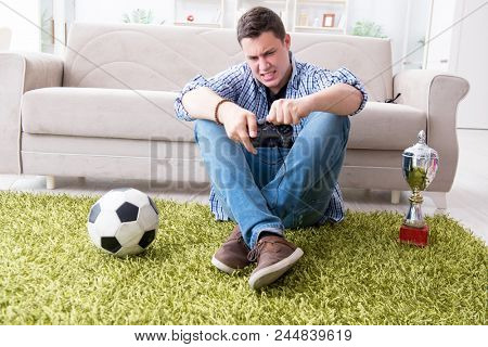 Young man playing computer games at home stock photo