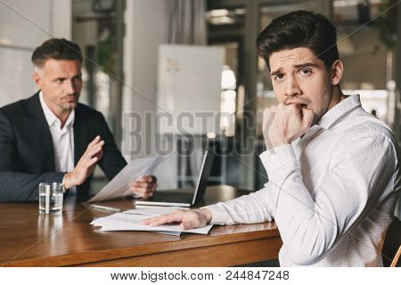 Business, career and placement concept - uptight nervous man worrying during job interview in office while negotiating with caucasian businessman or director stock photo