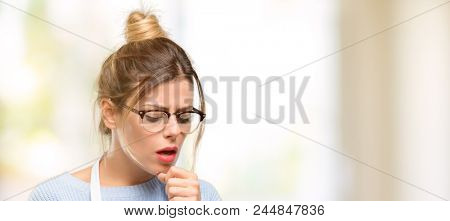 Young woman shop owner, wearing apron sick and coughing, suffering asthma or bronchitis, medicine concept stock photo
