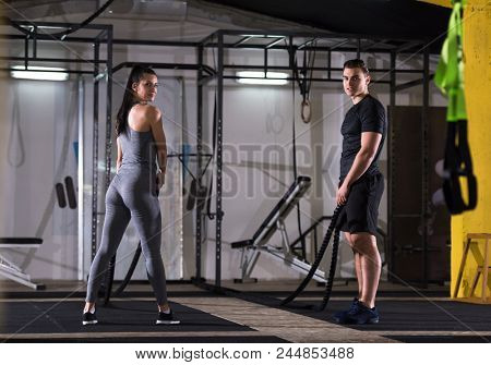 young fit sports couple working out in functional training gym doing  battle ropes cross fitness exercise stock photo